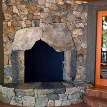 Mosaic style New England fieldstone fireplace & hearth with large weathered stones surrounding firebox