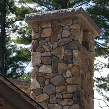 Custom chimney with tomahawk design crafted out of New England fieldstone with raised 6� thick granite cap