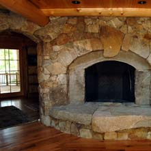 Double arched granite and fieldstone fireplace with large weathered stone hearth