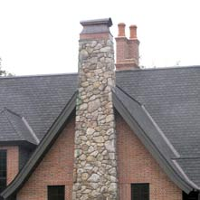 Fieldstone chimney with copper cap on an English Tudor style home