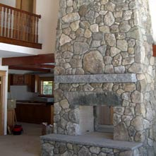 Pass-through fieldstone fireplace with antique granite lintel and Swenson gray granite mantel & hearth