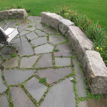 Natural joint bluestone patio with antique granite wall