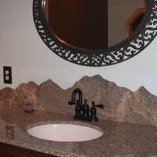 Hand cut, polished granite backsplash skillfully crafted by Chad P. Sanborn in the form of a mountain range