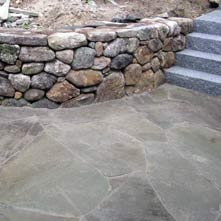 Curved fieldstone retaining wall with large irregular shaped bluestone patio & granite steps