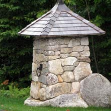 One of a pair of custom crafted entry posts atop an existing boulder
