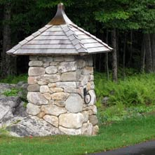 The second of a pair of custom crafted entry posts atop an existing boulder