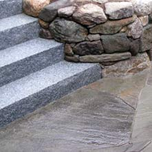 Fieldstone retaining wall with granite steps incorporated into stone work