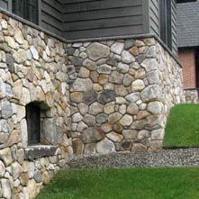 This mountain top retreat has a fieldstone veneer with Caledonia granite coping