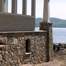 Tightly fitting fieldstone veneer on the exterior of a New Hampshire lake house with custom granite coping