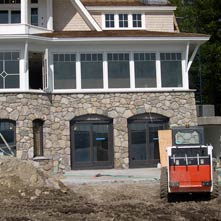 New England fieldstone veneer with granite recessed into arched windows